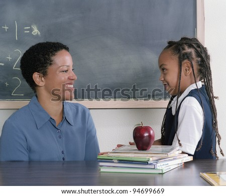 Teacher and school girl talking in classroom - stock photo