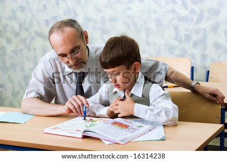 Teacher and schoolboy read alphabet. Primary school. - stock photo