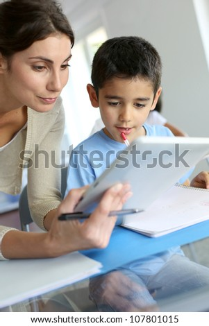 Teacher and schoolboy using electronic tablet in class