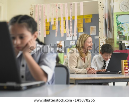 Teacher and schoolboy using laptop with girl in foreground at classroom - stock photo