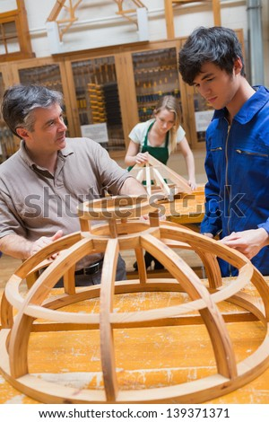 Teacher and student at a workbench in a woodworking class working on a frame - stock photo