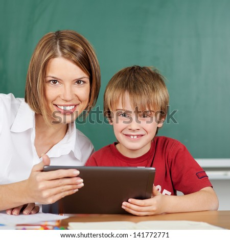 Teacher and student during lesson with tablet - stock photo