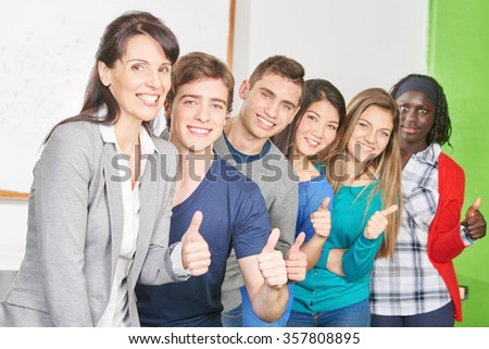 Teacher and students as a winning team in a high school classroom - stock photo