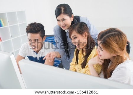 Teacher and students having fun at college using modern computers - stock photo