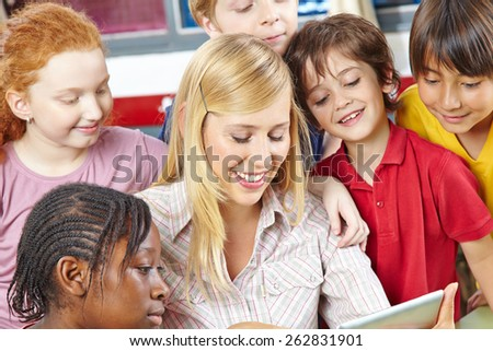 Teacher and students looking at tablet computer in elementary school class - stock photo