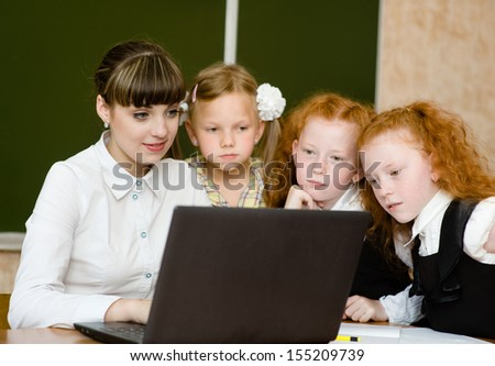 teacher and students use computers in the classroom - stock photo
