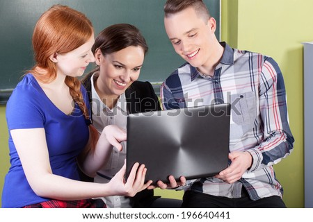 Teacher and students using laptop in classroom - stock photo
