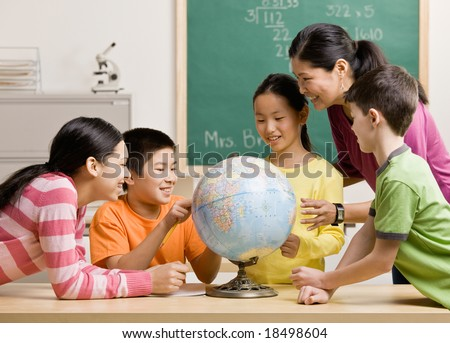 Teacher and students viewing globe in geography classroom - stock photo