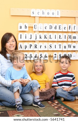 teacher and three preschoolers during lesson - stock photo