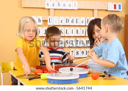 teacher and three preschoolers during music lesson - stock photo