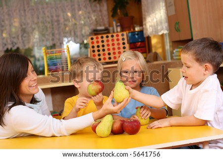 teacher and three preschoolers having break for fruit