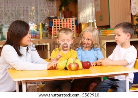 teacher and three preschoolers having break for fruits