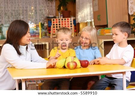 teacher and three preschoolers having break for fruits - stock photo