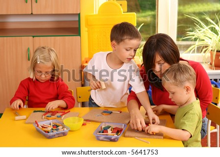 teacher and three preschoolers plazing with wooden blocks
