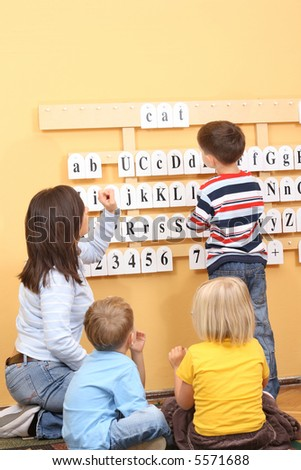 teacher and two preschoolers during lesson - stock photo