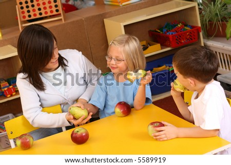 teacher and two preschoolers having break for fruits - stock photo