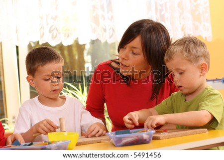 teacher and two preschoolers playing with wooden blocks - stock photo