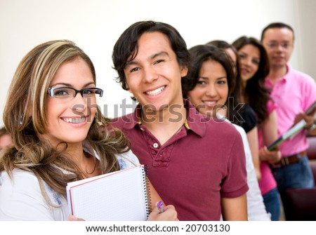 teacher and university students smiling in a classroom - stock photo