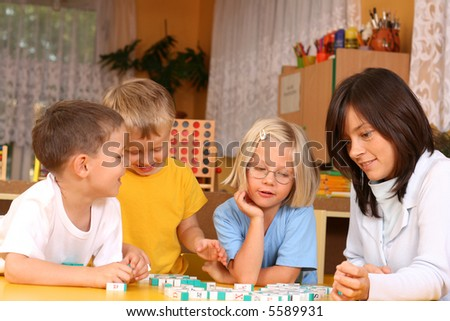teacher and 5-6 years old girl and boy learning with letters