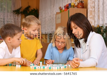 teacher and 5-6 years old girl and boys learning with letters - stock photo