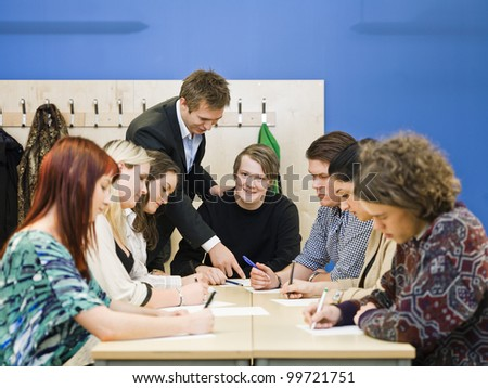 Teacher and young Adult students in the classroom - stock photo