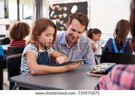 Teacher and young schoolgirl using tablet in classroom
