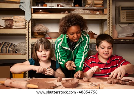 Teacher and young students having fun in clay studio - stock photo