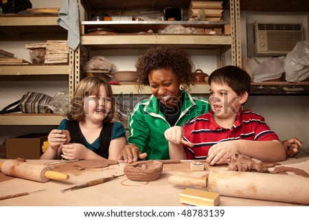 Teacher and young students having fun ion clay studio - stock photo