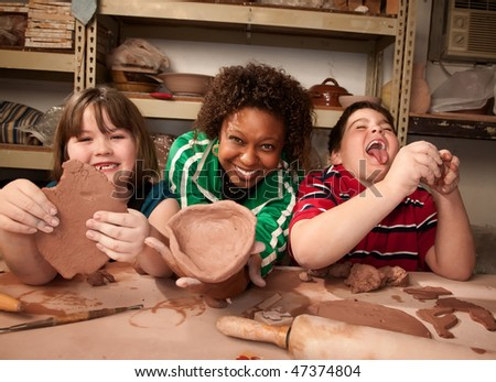Teacher and young students working on projects in clay studio - stock photo