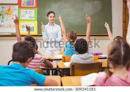Teacher asking a question to her class at the elementary school - stock photo