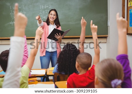 Teacher asking her students a question at the elementary school - stock photo