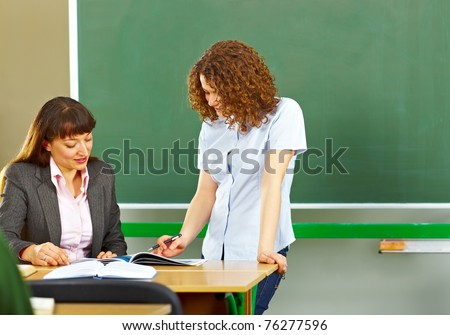 Teacher asking student at the school board and she is showing something - stock photo
