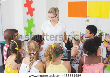 Teacher assisting kids in laboratory at school