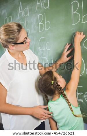 Teacher assisting schoolgirl to learn alphabet on chalkboard in classroom at school - stock photo