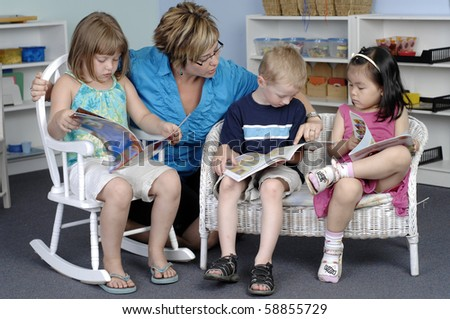 Teacher assists preschool boy and girls while they read books during their class. - stock photo