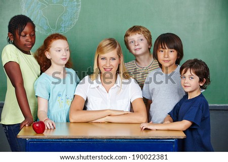 Teacher at desk with elementary school students in front of chalkboard