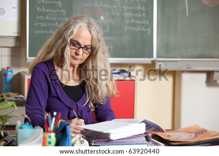 Teacher at her desk in class checking on the homework - stock photo