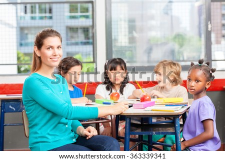 Teacher at primary school with multi race classroom. - stock photo