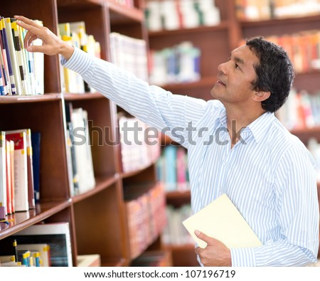 Teacher at the library looking for a book in the bookshelves - stock photo
