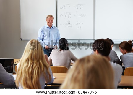 Teacher at university in front of a chalkboard - stock photo