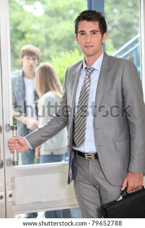 Teacher carrying briefcase opening door - stock photo
