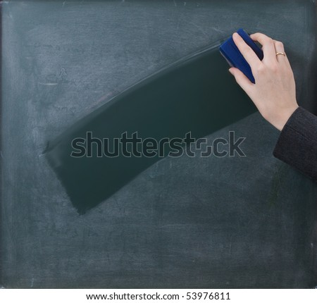 Teacher cleaning the chalkboard, suits centered composition - stock photo