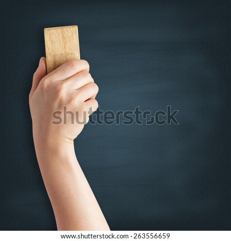Teacher cleaning the chalkboard with a chalk duster - stock photo