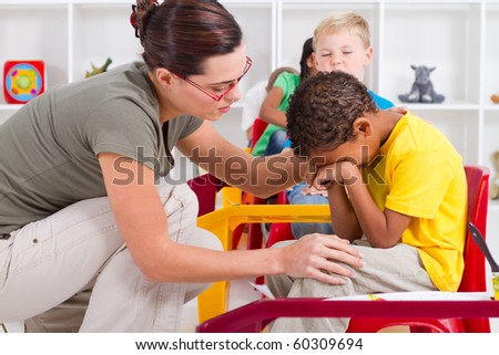 teacher comforting crying preschool boy - stock photo