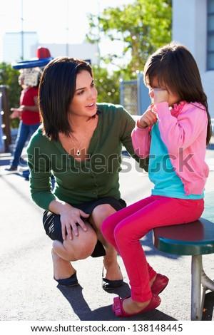 Teacher Comforting Upset Elementary School Pupil - stock photo