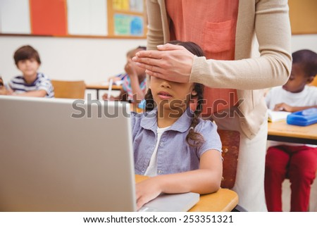 Teacher covering pupil eyes in front of the computer at the elementary school - stock photo
