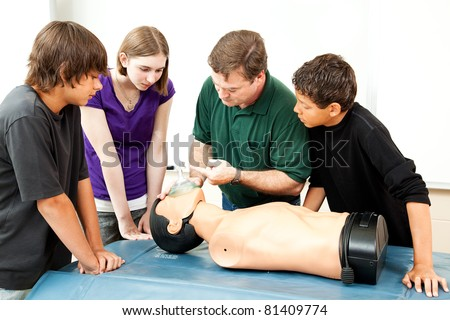 Teacher demonstrates to students how to use an oxygen mask for CPR. - stock photo