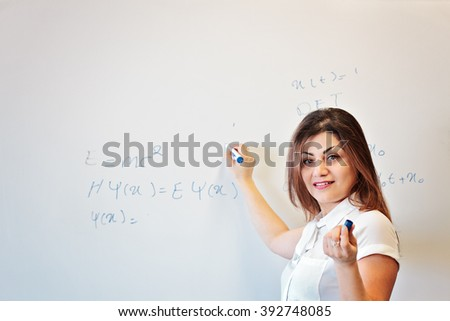 Teacher explain and write physics formula - stock photo