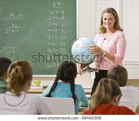 Teacher explaining globe to students - stock photo