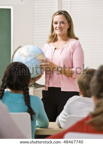 Teacher explaining globe to students - stock photo